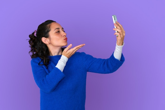 파란색 스웨터 포즈 보라색 배경에 고립에서 예쁜 젊은 여자. 사람들의 라이프 스타일 개념.