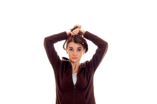 갈색 스포츠 옷을 입고 예쁜 젊은 여자가 정면을보고 흰 벽에 고립 된 포즈