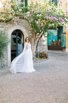 Милая молодая женщина в элегантном голубом платье представляя на предпосылке красивого старого здания с зацветая деревом, прогулкой в сирмионе, италии.