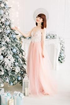 美しいクリスマスツリーの近くで、笑顔でカメラにポーズをとって、エレガントなドレスを着たかなり若い女性
