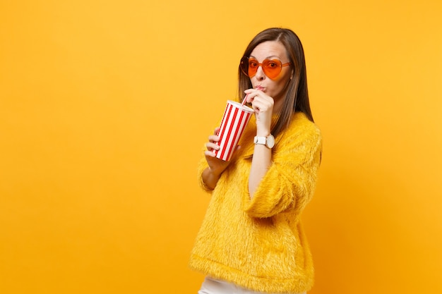 明るい黄色の背景で隔離のプラスチック製のコップからコーラやソーダを飲む毛皮のセーターとハートオレンジ色のメガネのかなり若い女性。人々の誠実な感情、ライフスタイルのコンセプト。広告エリア。