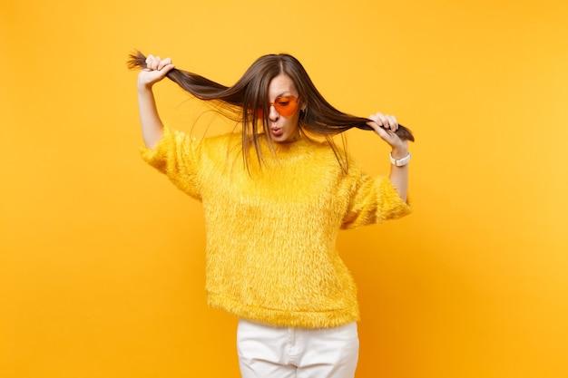Довольно молодая женщина в меховом свитере, сердце оранжевые очки дурачиться, держа ее волосы, как хвостики, изолированные на ярко-желтом фоне. люди искренние эмоции, концепция образа жизни. рекламная площадка.