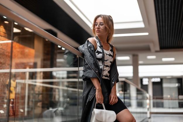 쇼핑 센터에 서있는 세련 된 가죽 배낭 스커트에 여름 코트에 패턴으로 트렌디 한 티셔츠에 안경에 예쁜 젊은 여자. 실내 현대 소녀. 미국식