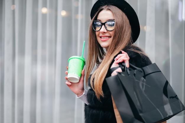 안경에 꽤 젊은 여자는 긴 쇼핑 후 그녀의 손에 커피 한잔과 함께 도시 주위를 걷고있다