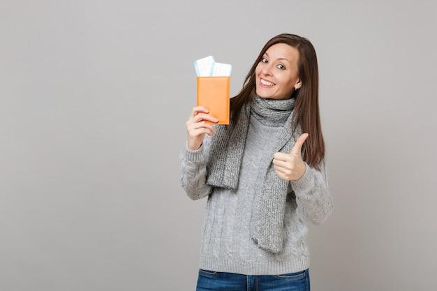 회색 스웨터를 입은 예쁜 젊은 여성, 엄지손가락을 치켜든 스카프, 여권을 들고 회색 배경에 격리된 탑승권. 건강한 패션 라이프스타일, 사람들의 진심 어린 감정, 추운 계절 개념.