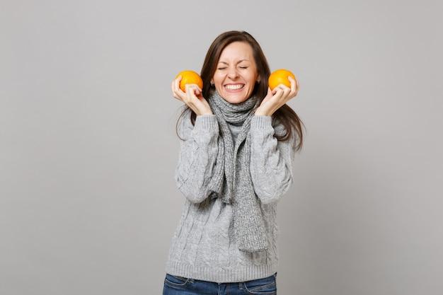 Довольно молодая женщина в сером свитере, шарфе с закрытыми глазами, держащими апельсины, изолированные на сером стенном фоне. люди здорового образа жизни моды искренние эмоции, концепция холодного сезона. копируйте пространство для копирования.