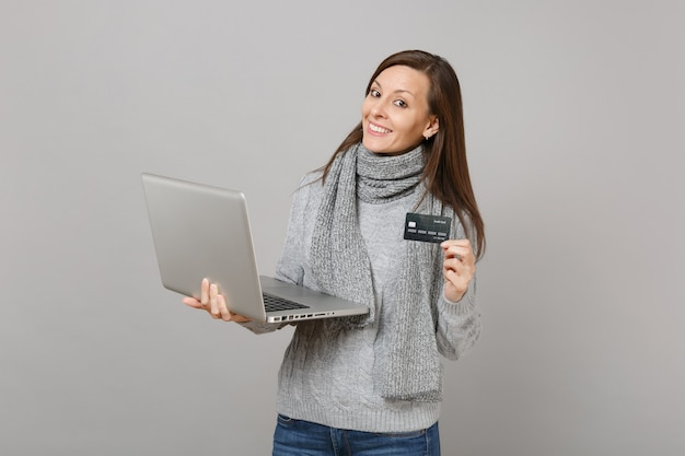 회색 스웨터를 입은 예쁜 젊은 여성, 노트북 컴퓨터에서 작업하는 스카프, 회색 벽 배경에 격리된 신용 은행 카드를 들고 있습니다. 건강한 생활 방식, 온라인 치료 컨설팅, 추운 계절 개념.