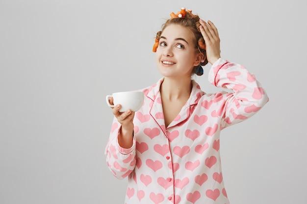 Довольно молодая женщина в бигуди и пижаме пьет утренний кофе