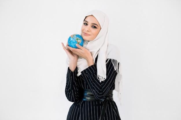 Милая молодая женщина в хиджабе обнимает маленький земной шар