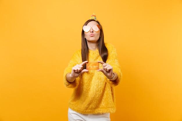 Довольно молодая женщина в оранжевых очках сердца день рождения шляпа дует губы, держа кредитную карту, наслаждаясь праздником, празднуя изолированные на желтом фоне. люди искренние эмоции, концепция образа жизни.