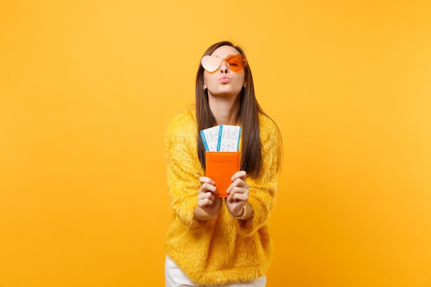 주황색 하트 안경을 쓴 예쁜 젊은 여성이 입술을 불고, 공기 키스를 보내고, 여권을 들고, 노란색 배경에 격리된 탑승권 티켓을 들고 있습니다. 사람들은 진실한 감정, 라이프 스타일. 광고 영역입니다.
