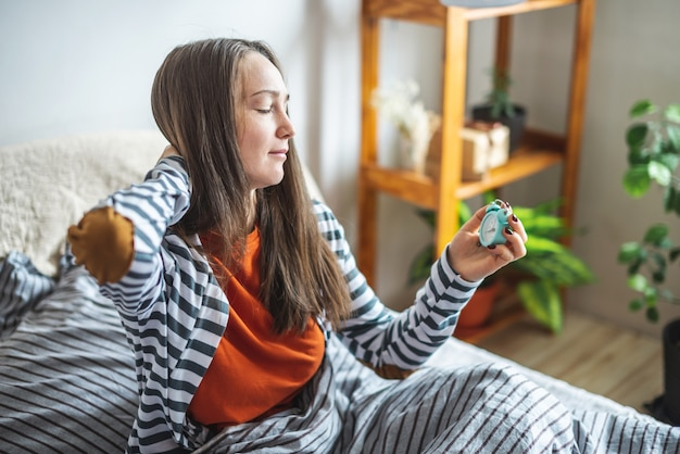 Довольно молодая женщина в пижаме сидит в постели утром, потягивается и держит будильник