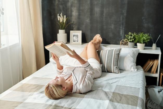 Довольно молодая женщина в пижаме расслабляется на кровати на досуге и читает книгу, оставаясь дома в выходные