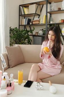 目の下のパッチと朝食のためにオレンジを切るソファに座っているパジャマのかなり若い女性