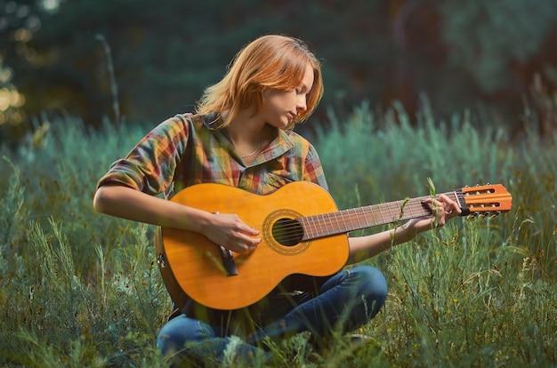 Довольно молодая женщина в клетчатой рубашке и синих джинсах играет на акустической гитаре