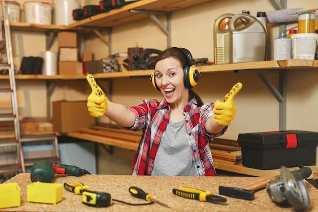 Довольно молодая женщина в клетчатой рубашке, серой футболке, шумоизолированных наушниках, желтых перчатках показывает палец вверх, работает в столярной мастерской за деревянным столом с куском дерева, различными инструментами.