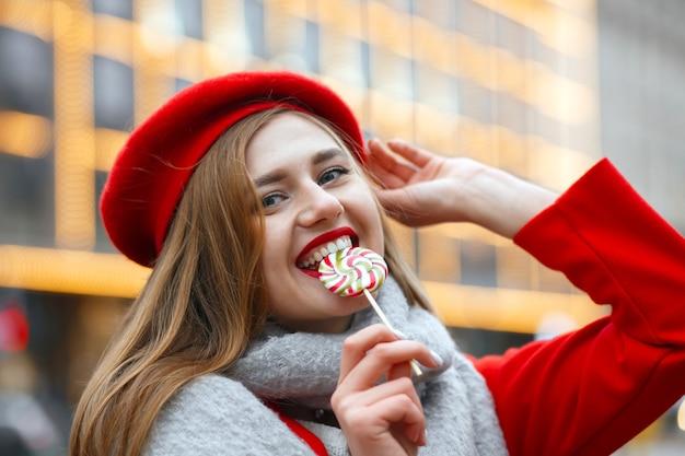 甘いお菓子を噛む赤いコートのかなり若い女性。空きスペース