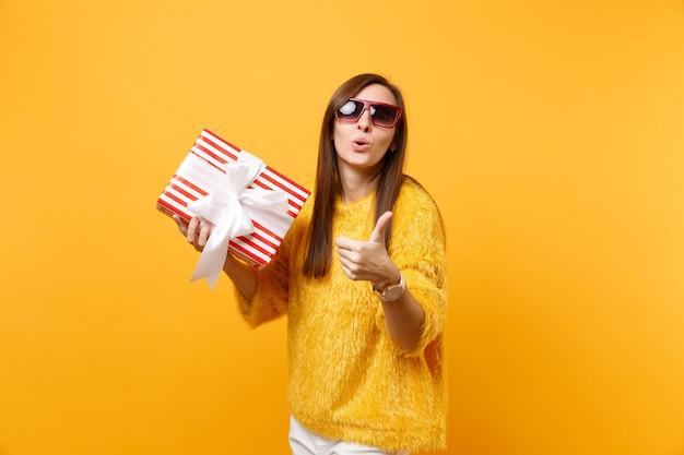 明るい黄色の背景に分離されたギフトプレゼントと赤い箱を保持している親指を示す唇を吹く赤い眼鏡のかなり若い女性。人々の誠実な感情、ライフスタイルのコンセプト。広告エリア。