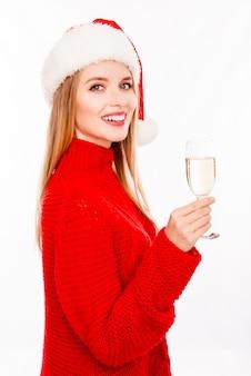 Довольно молодая женщина в шляпе санта-клауса с бокалом шампанского