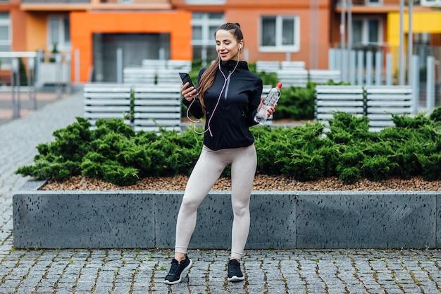 朝のランニングの後、新鮮な空気に水とヘッドフォンを装着した、スポーツウェアを着たきれいな若い女性。健康的なコンセプト。