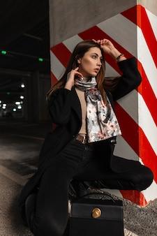 革のバッグが付いているブーツの絹の優雅なスカーフが付いているスタイリッシュな黒いコートのかなり若い女性は、赤白の線で柱の近くの駐車場のアスファルトに座っています。アーバンガールのファッションモデルは屋外で休んでいます。