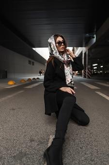 トレンディな黒のアウターウェアのダークファッショナブルなサングラスの頭にヴィンテージシルクスカーフのスタイリッシュな服を着たかなり若い女性が屋外でポーズします。ファッショナブルな女の子は、街の道路でリラックスします。優雅。