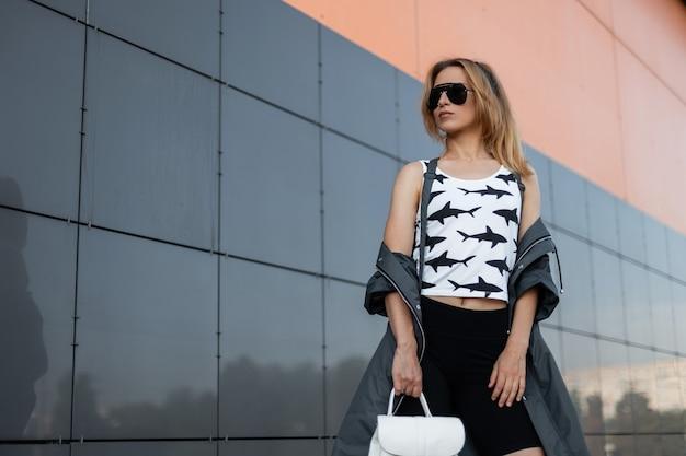 현대적인 건물 근처 거리에서 포즈를 취하는 가죽 배낭과 흰색 무늬 티셔츠에 트렌디 한 선글라스에 세련된 재킷에 예쁜 젊은 여자. 도시에있는 나가서는 소녀.