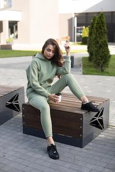 街の木製のベンチに座って、温かい飲み物を持っているスタイリッシュなスポーツウェアのかなり若い女性。女性のファッション。都市のライフスタイル