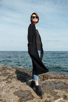 선글라스와 해변에 서있는 검은 코트에 예쁜 젊은 여자
