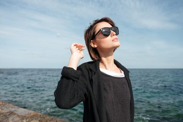 晴れた天気で海の近くを歩くサングラスをかけたかなり若い女性