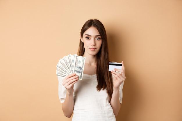Довольно молодая женщина в белой блузке, показывая долларовые купюры и пластиковую кредитную карту, бесконтактную оплату против наличных денег, стоя на бежевом.