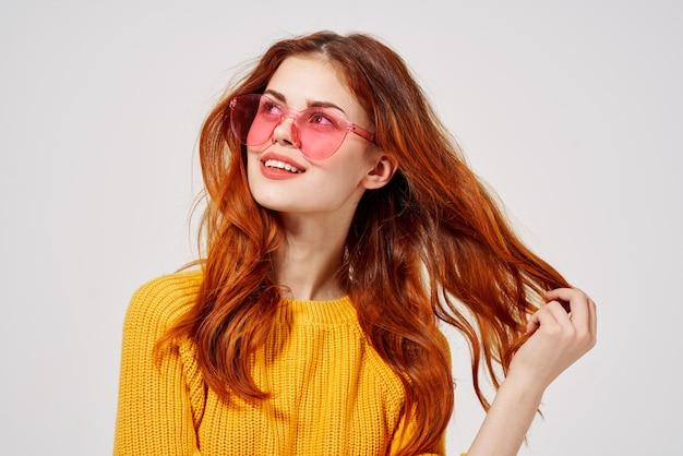 Довольно молодая женщина в желтом свитере и джинсах позирует в розовых очках. фото высокого качества