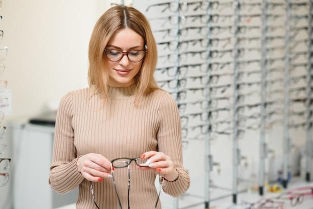 Довольно молодая женщина выбирает новые очки в магазине оптики