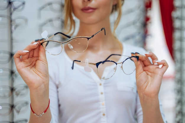Pretty young woman is choosing new glasses at optical store