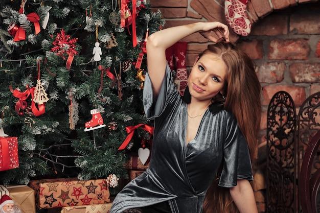 Довольно молодая женщина сидит у елки с украшенной гостиной с камином. девушка окружена новогодними украшениями и подарками. концепция уютного празднования нового года. копировать пространство