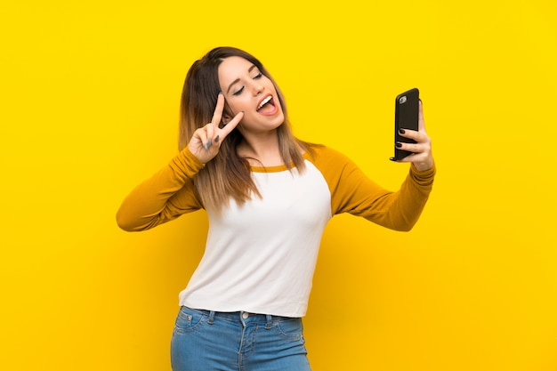 Pretty young woman over isolated yellow wall making a selfie