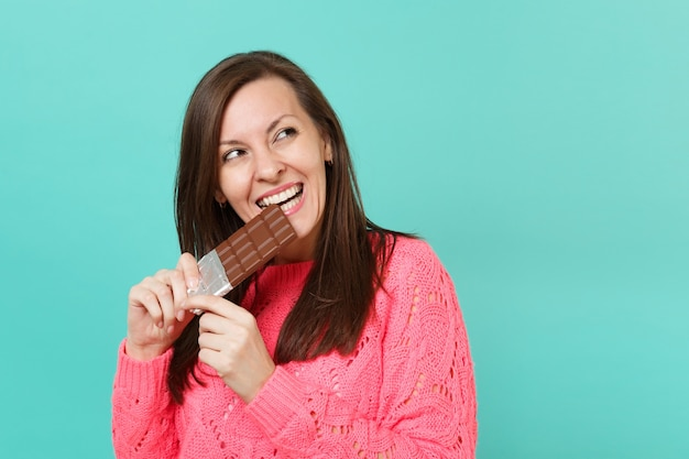 Pretty young woman in knitted pink sweater holding in hand biting chocolate bar looking aside isolated on blue turquoise wall background, studio portrait. people lifestyle concept. mock up copy space.