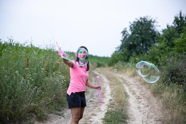 Una bella giovane donna lancia enormi bolle di sapone sullo sfondo della bellissima natura.