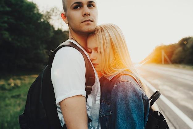 Довольно молодая женщина, опираясь на грудь парня и держа глаза закрытыми, стоя на обочине дороги на природе