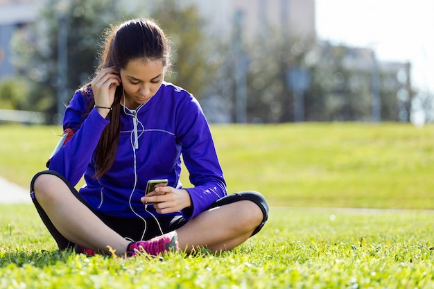 Pretty young woman listening to music after running.