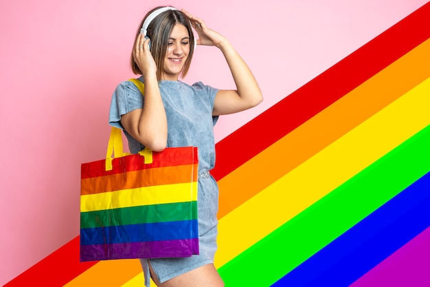 Pretty young woman listening to music on rainbow flag background