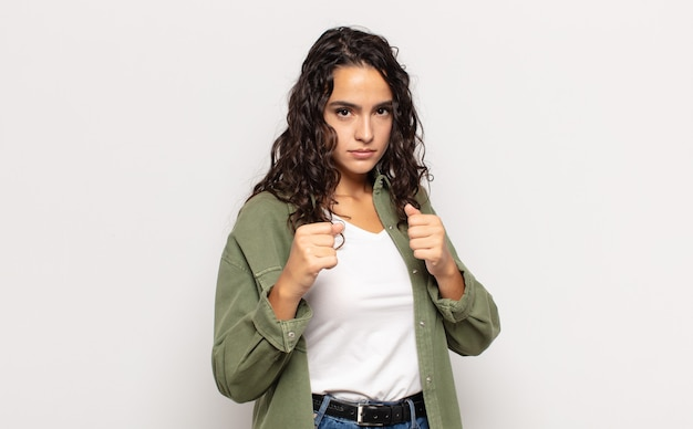 Pretty young woman looking confident, angry, strong and aggressive, with fists ready to fight in boxing position