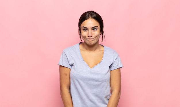 Pretty young woman looking goofy and funny with a silly cross-eyed expression, joking and fooling around