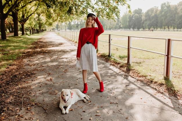 彼女の素敵な犬の屋外で幸せそうに見えるかなり若い女性。赤いプルオーバーと秋の公園で楽しんでいるスタイリッシュな靴で陽気なブロンド。