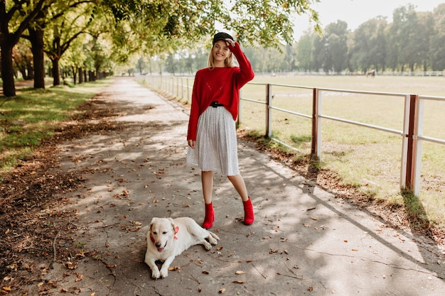 Pretty young woman looking happy with her lovely dog outdoor. cheerful blonde in red pullover and stylish shoes having fun in the autumn park.