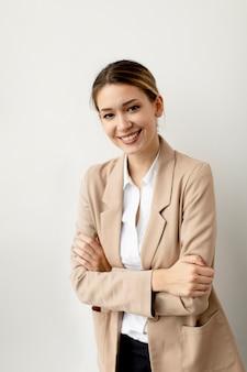 Довольно молодая женщина, выглядящая счастливой, гордой и довольной, улыбаясь, скрестив руки на белой стене