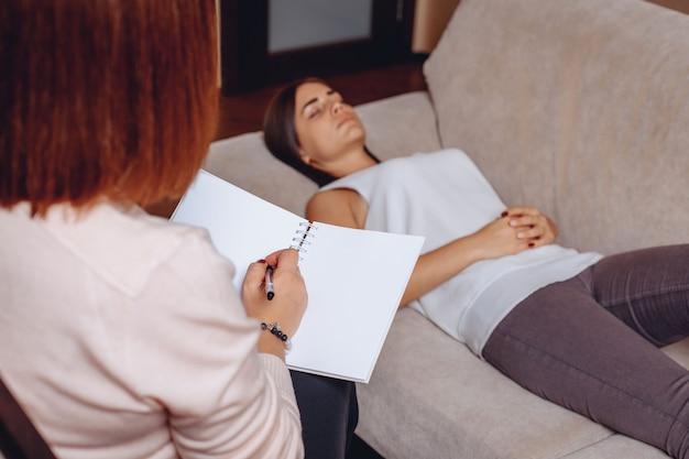 Pretty young woman lying on the couch at the reception with a psychotherapist. mental psychological problems. mental problems concept