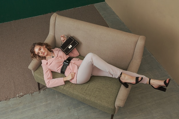 Pretty young woman lying on the couch in a stylish smart casual outfit with a small dark velvet hand bag.