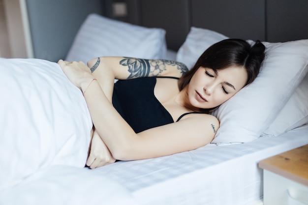 침대에 누워있는 예쁜 젊은 여자는 일어나고 싶지 않다