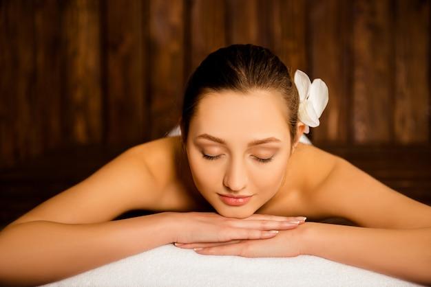 Довольно молодая женщина, лежа в сауне и расслабляясь
